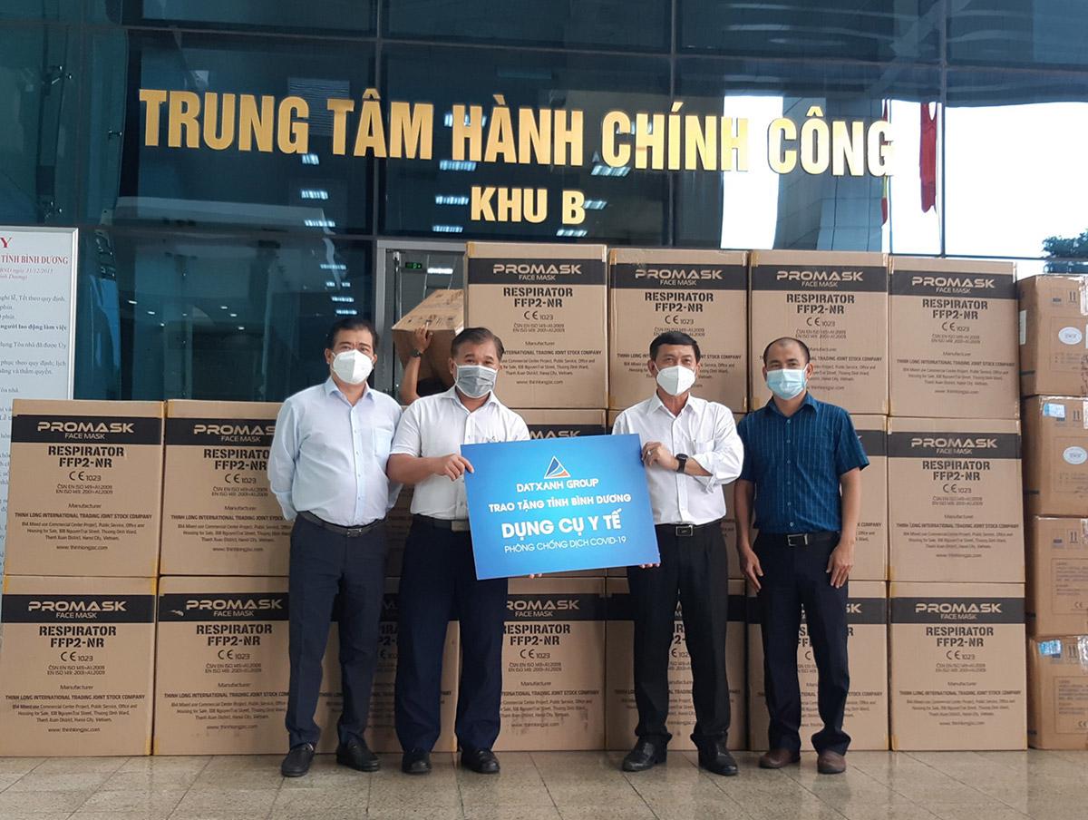 Đại diện Tập đoàn Đất Xanh trao tặng khẩu trang y tế N95 và bộ đồ bảo hộ cho ông Nguyễn Văn Lộc, Chủ tịch Ủy ban MTTQ tỉnh Bình Dương.